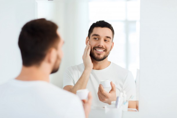 Attractive man using face cream