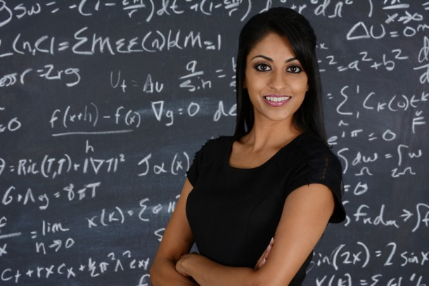Beautiful woman in front of blackboard with mathematical equations