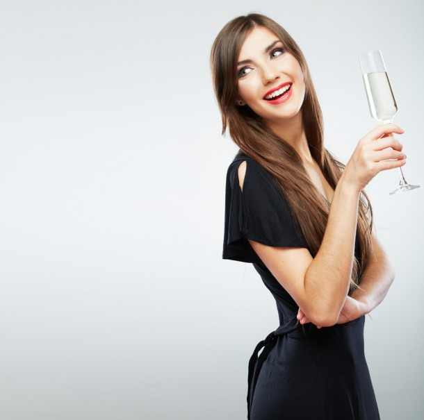 Beautiful woman in black dress with glass of champagne
