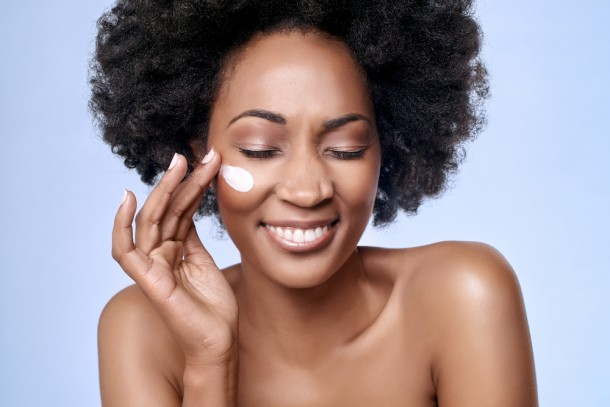 Beautiful African American woman using face cream