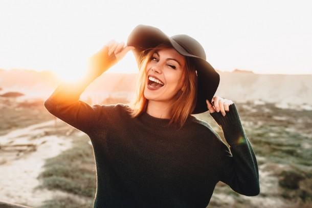 Beautiful, happy woman in black hat on beach